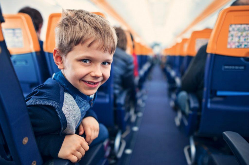 Kind auf einem eigenen Sitzplatz im Flugzeug