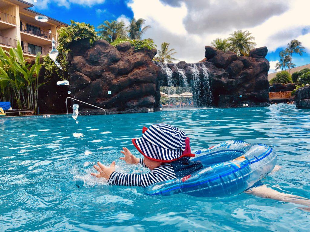 Im Schwimmring mit Wasserfontainen spielen