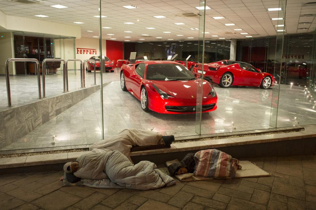Arm und reich beieinander. Obdachlose in Kapstadt schlafen vor der Ferrari Filiale